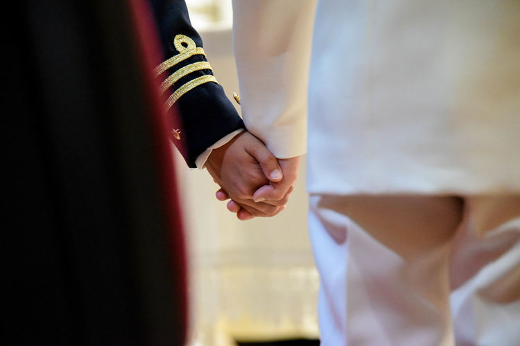 Midsection of men in uniform holding hands