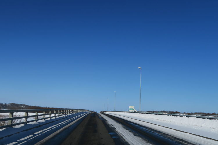 Road against clear blue sky during winter