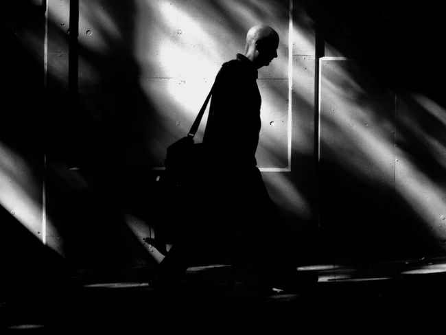 Man Bald Walking Side View Partial Silhouette Shadow And Light Concrete Wall Black And White Street Photography Laptop Bag