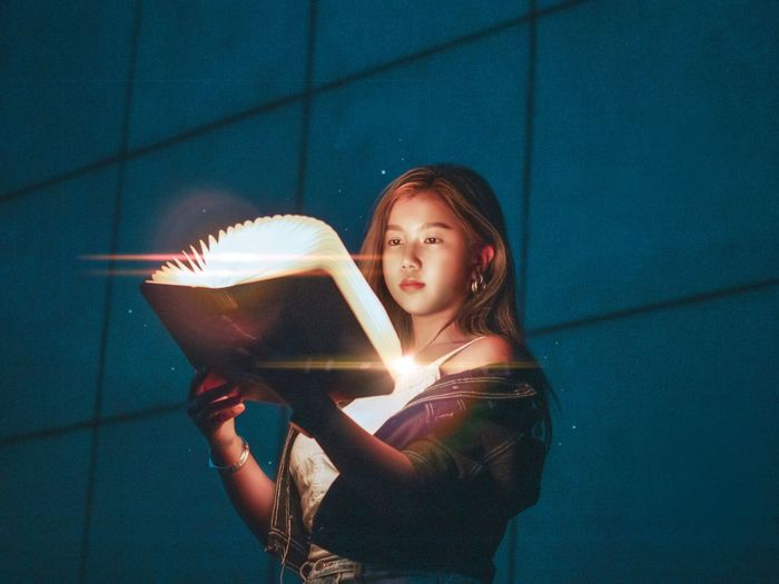 Portrait of a beautiful young woman holding illuminated lamp