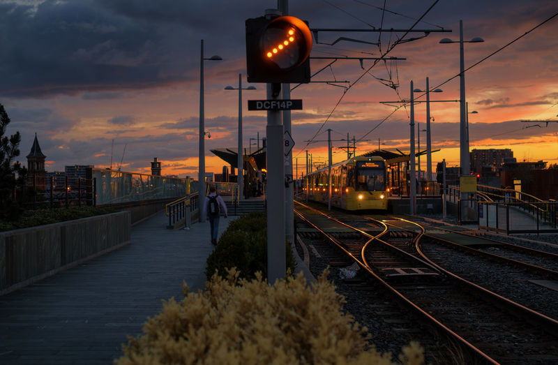 a tram station Illuminated Sunset Railroad Track Rail Transportation Railroad Station City Sky Cloud - Sky Railway Signal Railroad Station Platform Railroad Platform Railroad Crossing Train - Vehicle Passenger Train Street Light Public Transportation Metro Train