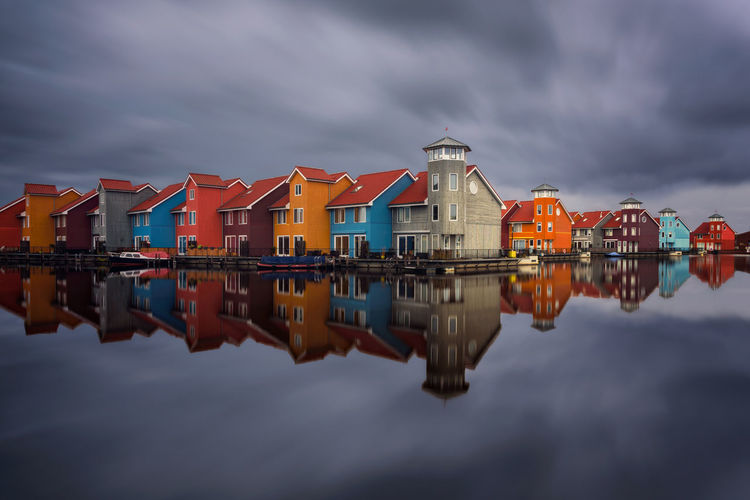 Reflection of multi colored houses in lake against cloudy sky