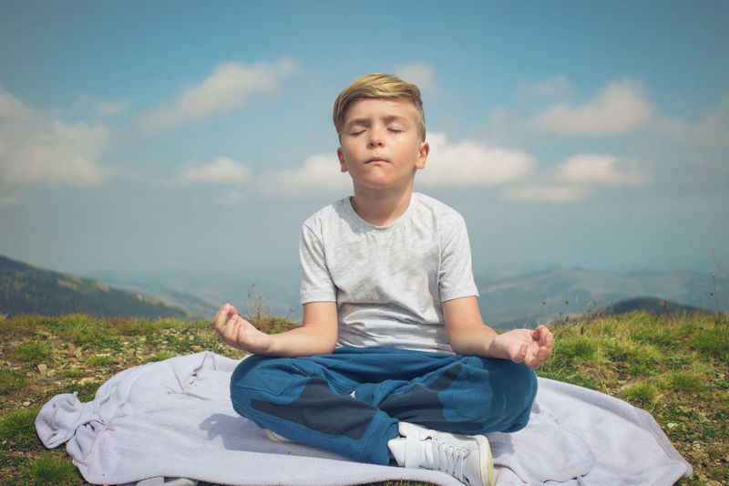 Small boy with eyes closed meditating in lotus position on a meadow.