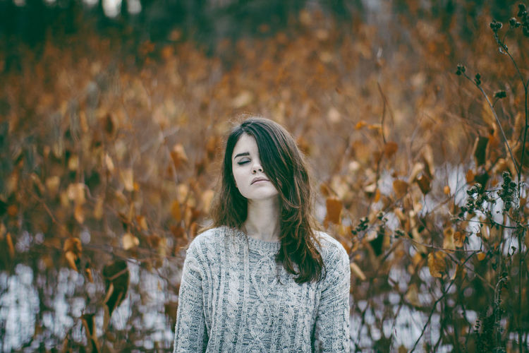 Thoughtful Woman Wearing Sweater Standing Against Dry Plants