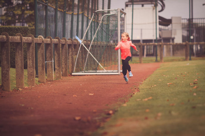 Young blond girl exercising on running track Exercising Running Age 6-9 Assertiveness Challenge Day Discipline Full Length Lifestyles One Person Outdoors People Perseverance Real People Running Running Track Sports Clothing Sports Race Track Young Girl