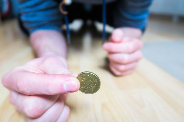 male sitting on wooden floor holding euro coin Coin Currency Finance Finding New Frontiers