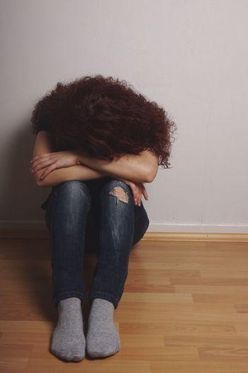 Full length of sad woman sitting on hardwood floor against wall