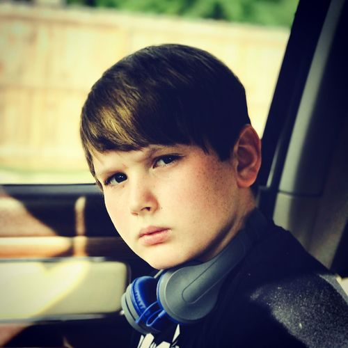 Close-up portrait of boy with headphones in car