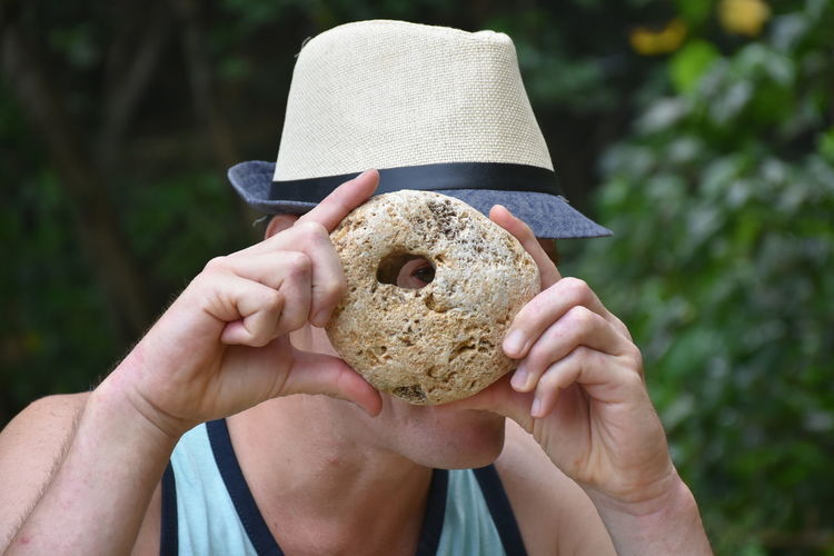 Close-up of man looking through hole in stone