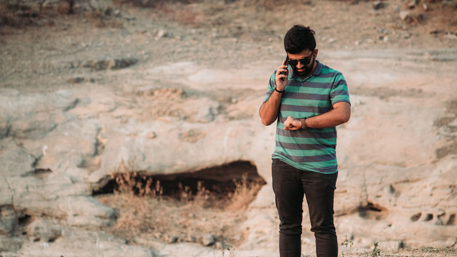 Young man talking on phone while standing on rock