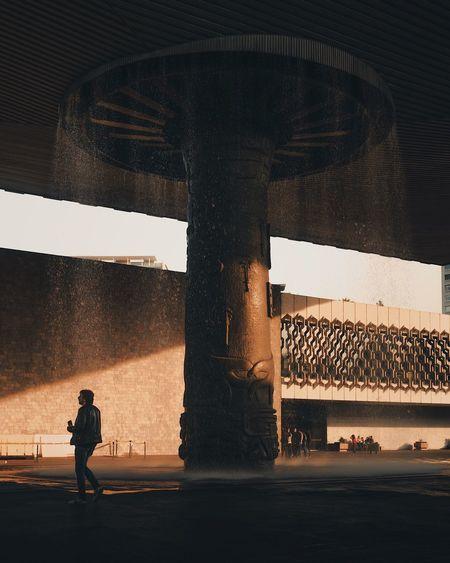Silhouette man standing on bridge in city