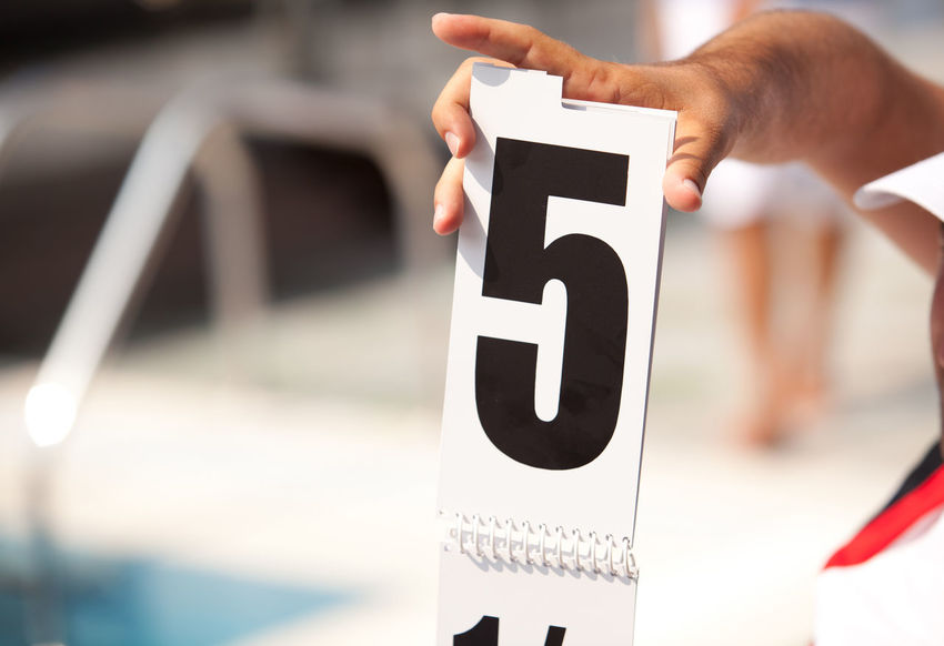 A referee showing number five during a competition. 5 Compete Icon Mark Numerical Referee Sign Competition Counting Evaluate Evaluation Five Grade Holding Judge Judgement Mathematics Number Numeric Position Showing Symbol