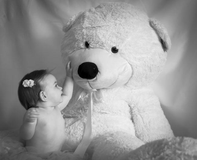 Cute girl with huge teddy bear against curtain