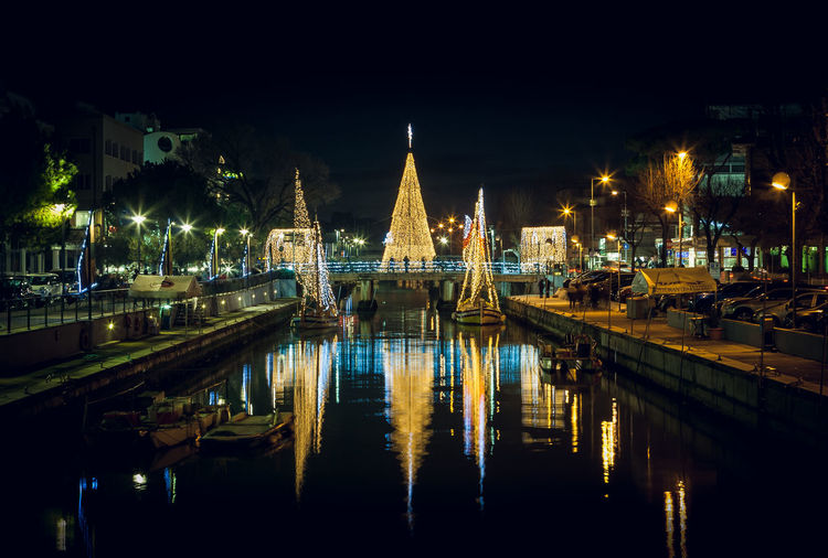 Scenic view of the Christmas Tree on a bridge at night, with reflections. Long exposure picture in Riccione, Emilia Romagna, Italy. Riccione Christmas New Year Around The World New Year Decoration Celebration Ice Carpet Port Harbor Emiliaromagna Italy Long Exposure Water Reflection Waterfront Long Exposure Shot Sunset Cloud - Sky Nautical Vessel Sailboat No People Illuminated Night Architecture Building Exterior Sky Built Structure River Nature City Travel Destinations Outdoors Bridge