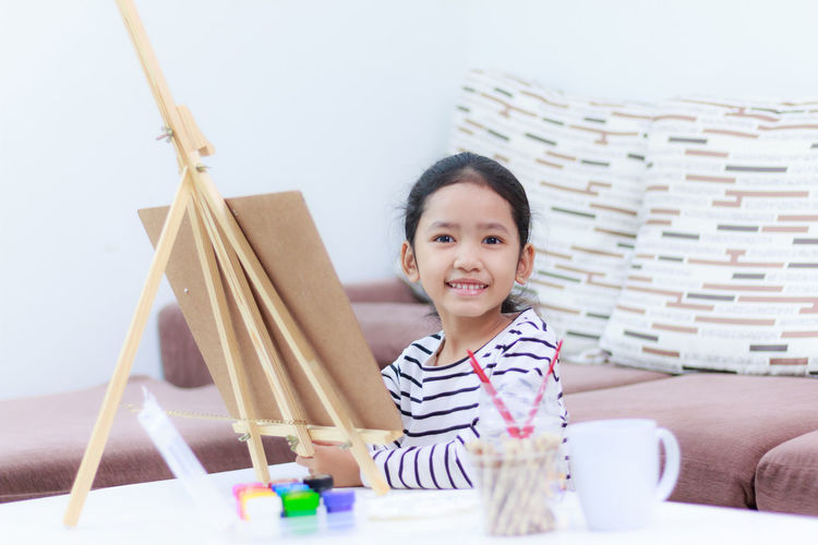 Portrait Of Girl Painting On Easel