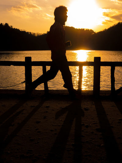 Side view of silhouette man on lake against sunset sky