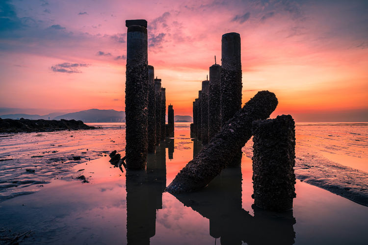 Reflection of wooden post in sea against sky during sunset