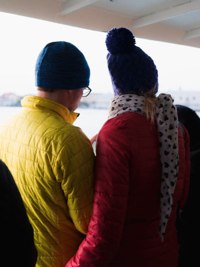 Rear view of couple walking in snow during winter
