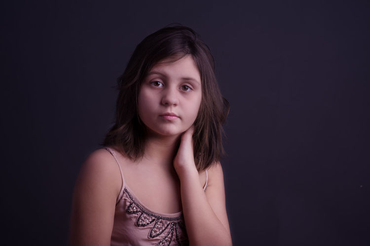 Portrait of girl with hand on neck against gray background