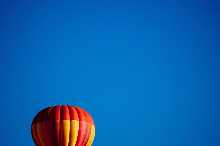 Cropped image of hot air balloon against clear blue sky