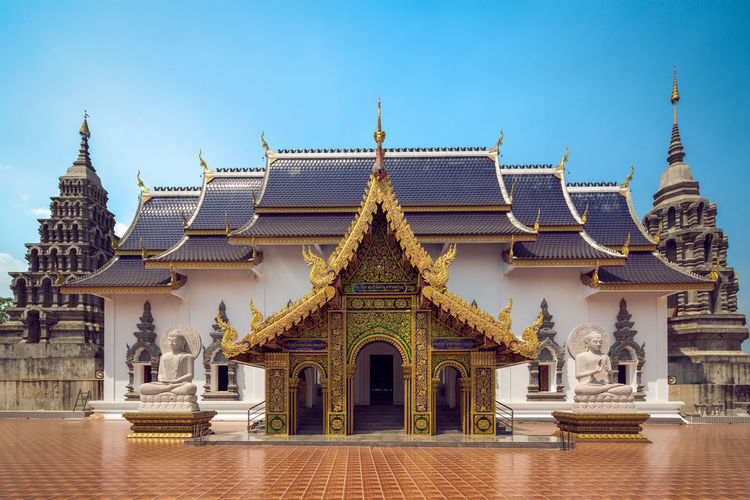 Exterior of buddhist temple against clear blue sky