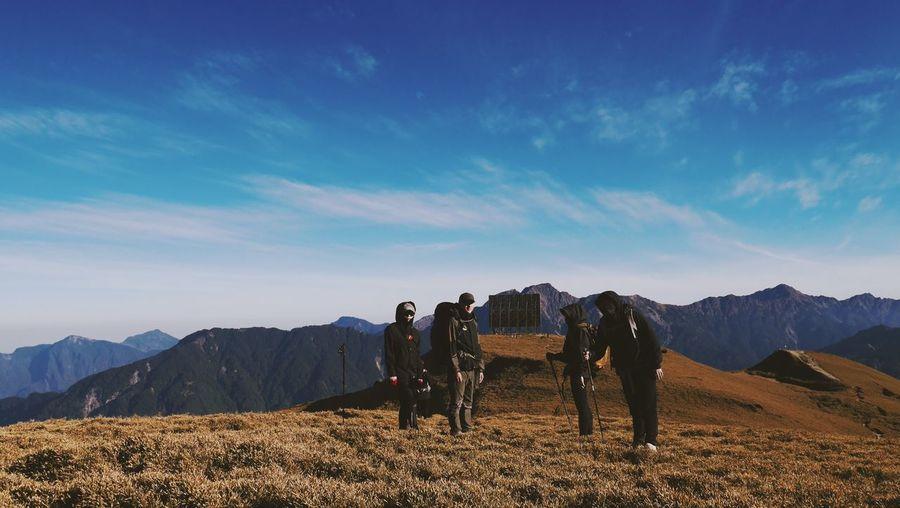 People on field against mountain range