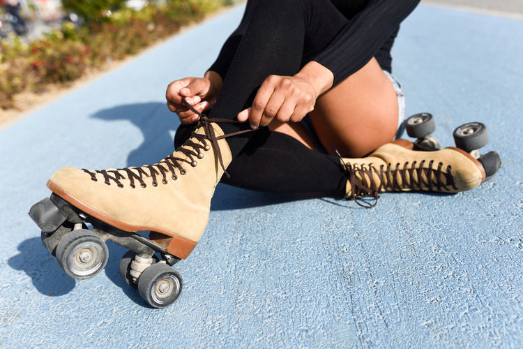 Woman Tying Shoelace Of Roller Skates