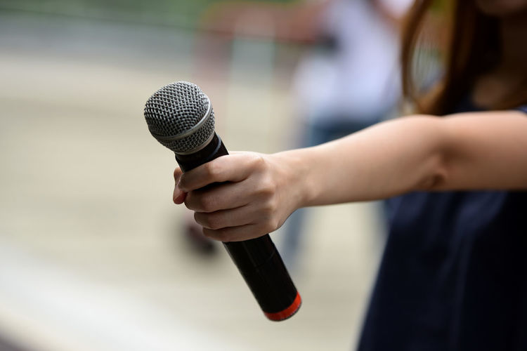 Midsection of woman holding microphone