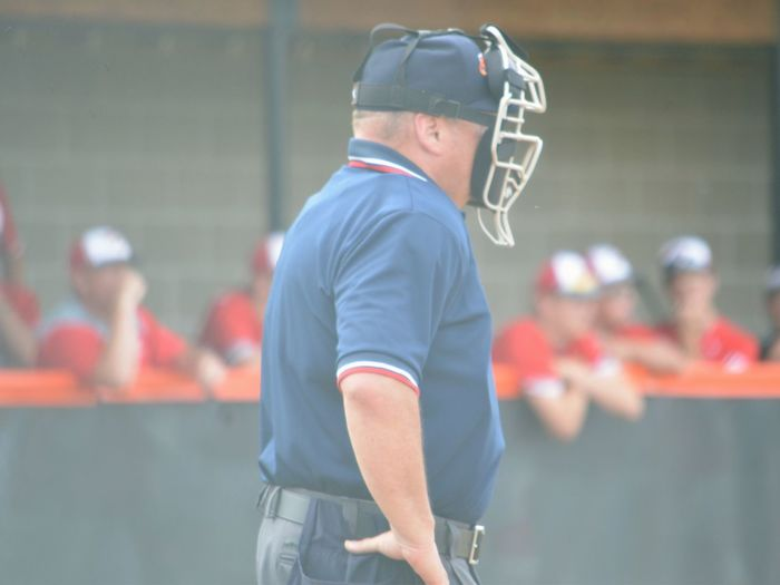 Side View Of Baseball Umpire With Hand On Hip Wearing Helmet