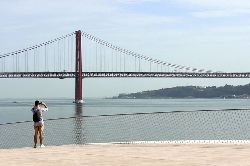 Rear view of man photographing 25 de abril bridge over tagus river against sky
