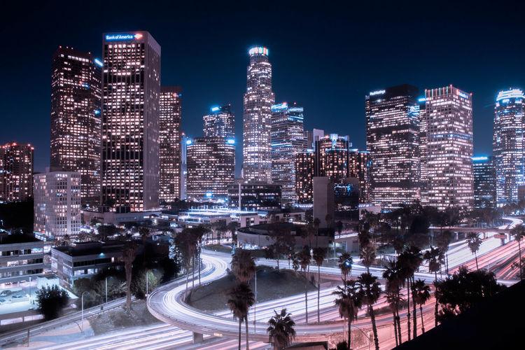Light trails on street in illuminated city at night