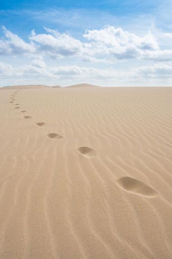 Footprints on sand in desert against sky