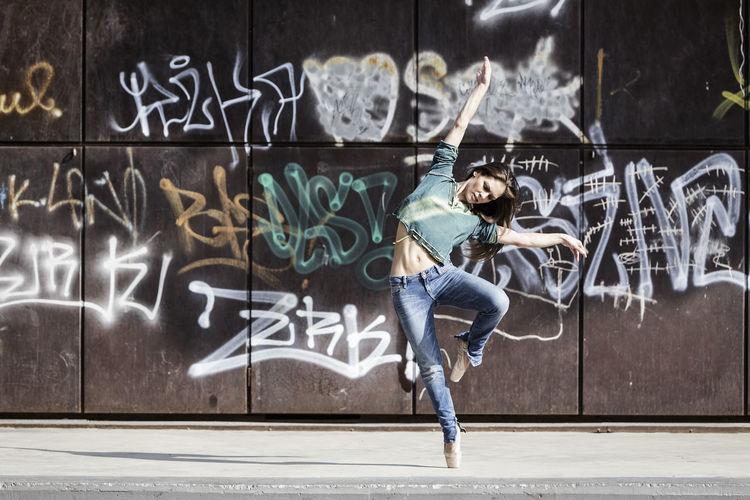 Full length of woman dancing against graffiti on wall