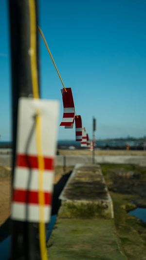A clothes line of red & white striped plastic cards to mark off limits to Rock Pool in Austinmer.