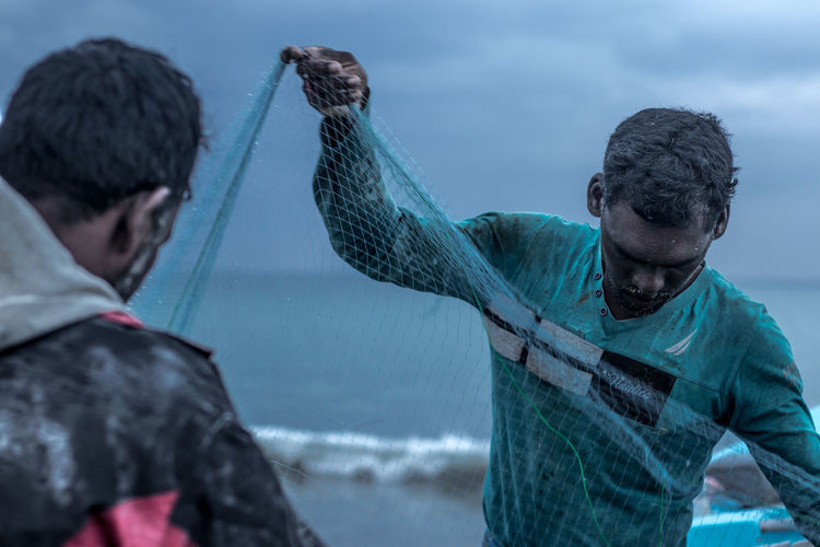 I was walking around the beach when I saw a bunch of fishermen net-fishing and pulling out their catch of the day from the sea. All of these pictures are moments I captured from the scene. My favourite is the one with the man wearing a cap which reads 'Void' and sorts out the fish as crows lurk behind him, hoping to get some of the catch. The Portraitist - 2018 EyeEm Awards Adult Animal Wildlife Animals In The Wild Casual Clothing Day Fish Fisherman Fishing Headshot Males  Marine Men Nature Nautical Vessel Outdoors People Sea Two People Vertebrate Water