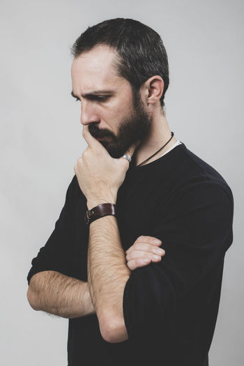 Bearded worried man on grey background. Lifestyles Males  Men Black Color Front View Gray Mid Adult Gray Background Mid Adult Men Contemplation Standing Young Men White Background Young Adult Facial Hair Beard Indoors  One Person Studio Shot Indoors  Males