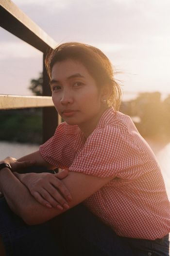 Portrait Of Woman Crouching By Railing During Sunset