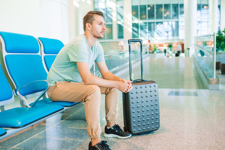 Full length of young man sitting on seat in airport