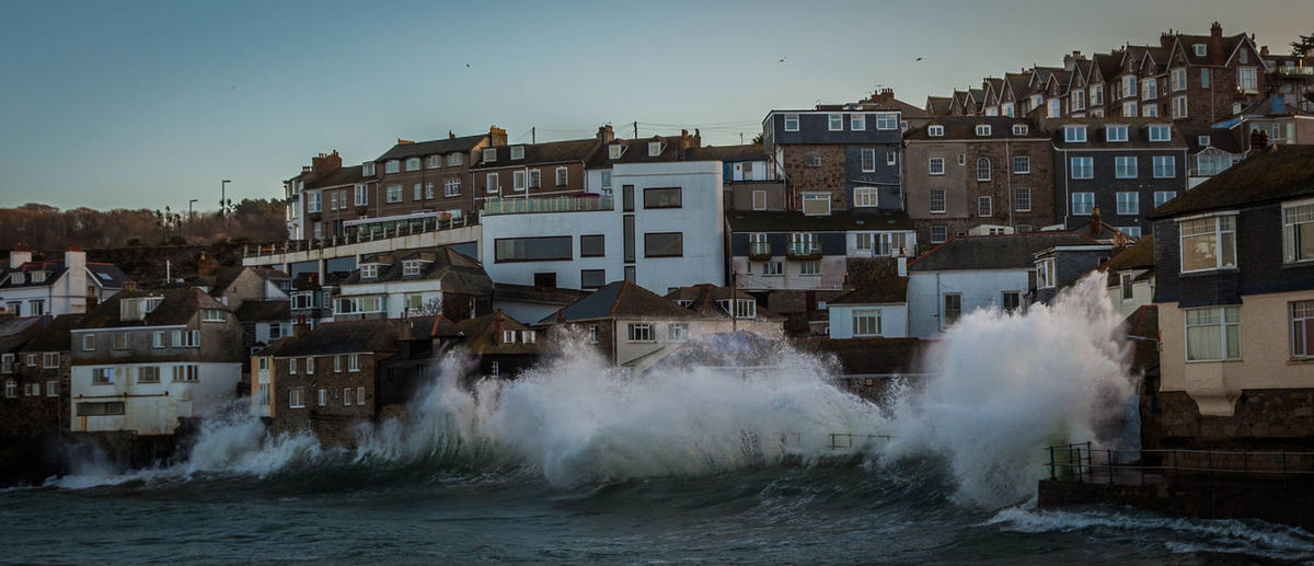 Waves splashing on shore by residential district against sky