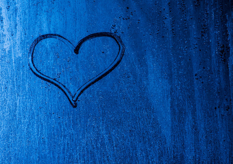 Close-up of heart shape on blue wall