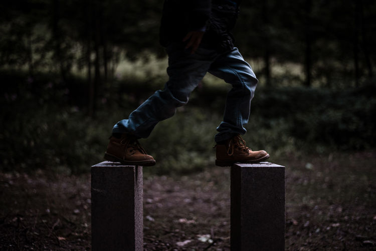Low Section Of Teenage Boy Balancing On Wooden Posts At Forest