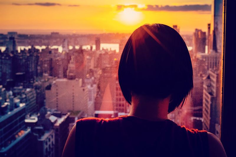 Rear view of woman overlooking cityscape during sunset