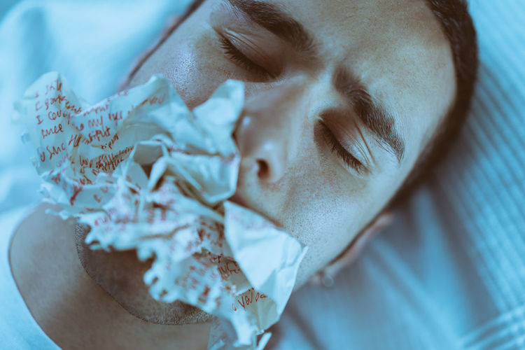 Close-up of young man with eyes closed eating paper while lying on bed at home