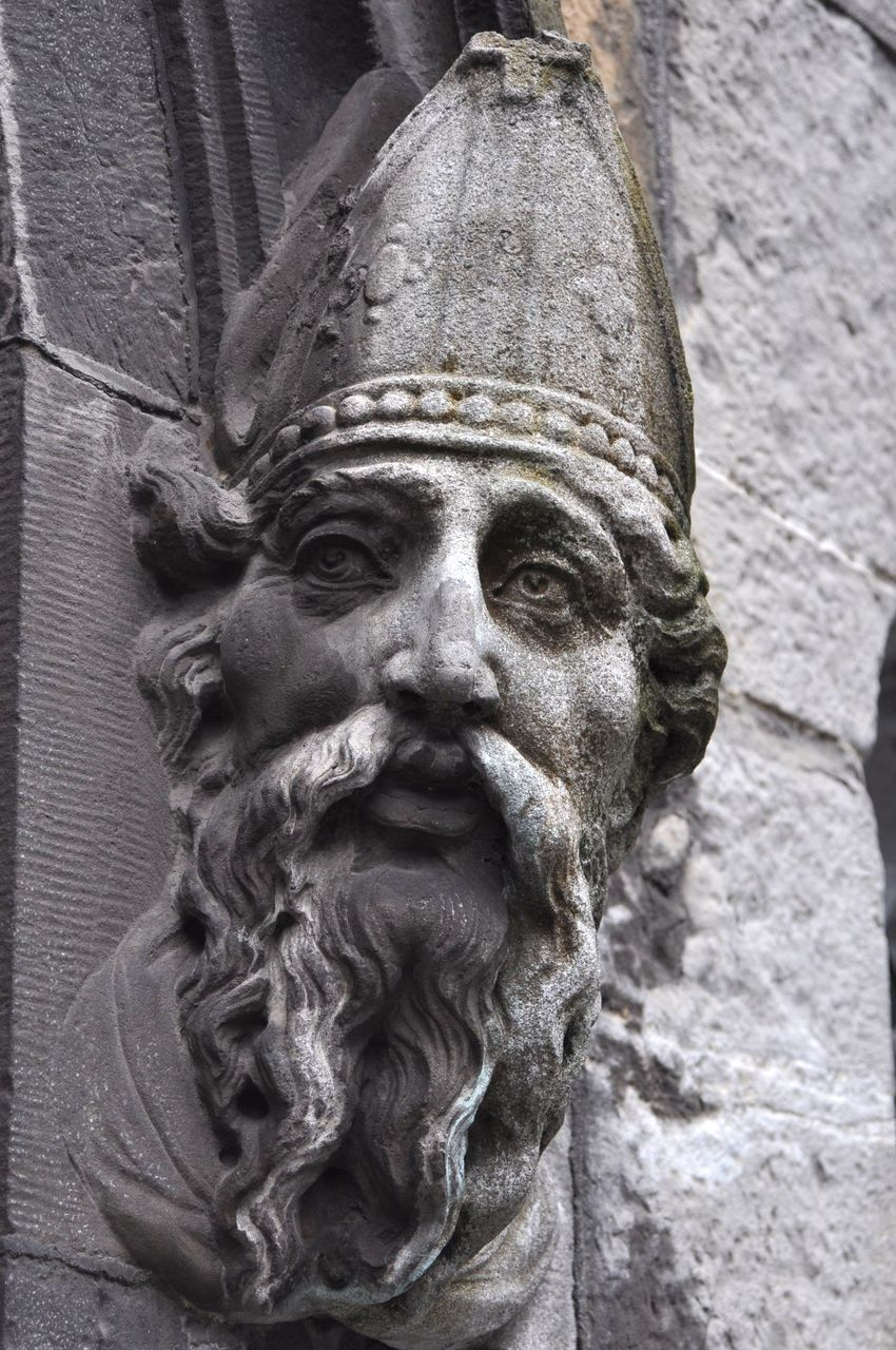 CLOSE-UP OF OLD STATUE AGAINST WALL