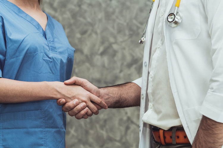 Midsection of doctor and patient shaking hands at clinic
