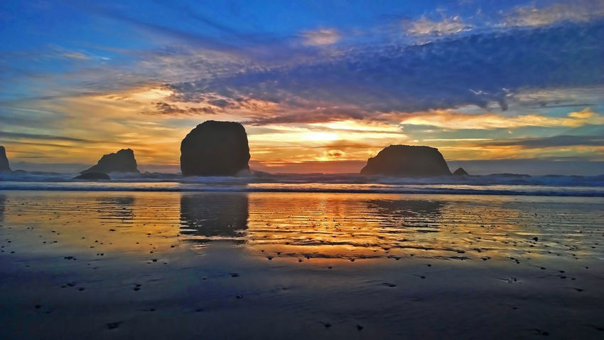 Beach Clouds Horizon Over Water Horizontal Symmetry Ocean Oregon Oregon Coast Oregon Sunset Oregoncoast Outdoors Reflection Rock Sand Scenics Sea Shore Sky Sun Sunset Sunset Reflection Vacations Water Waves West Coast