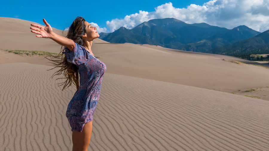 Young woman standing on sand at desert against sky