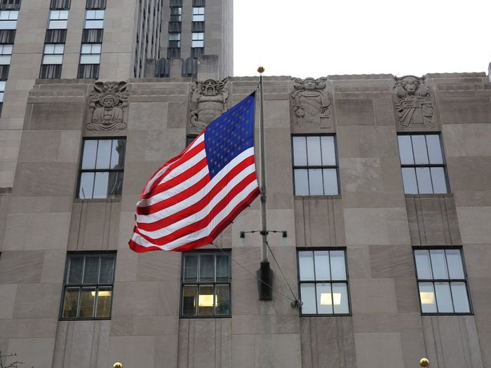 Low angle view of flag against building in city