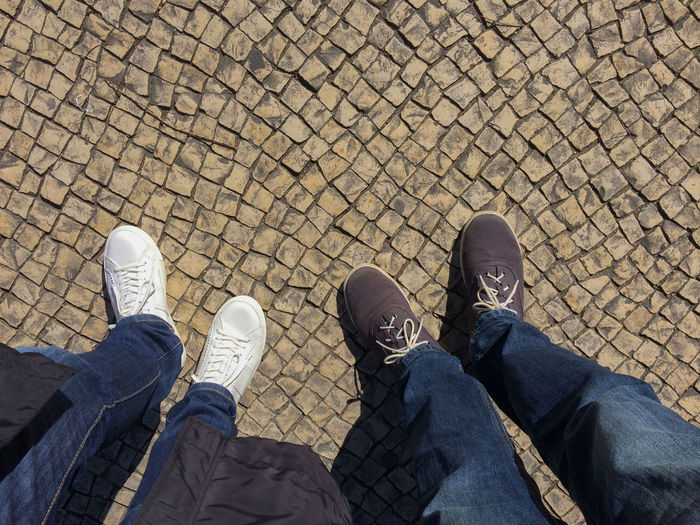 Two pairs of legs wearing casual shoes on the portugal traditional stone pavement. Top view shot. Lisboa Portugal Lisbon - Portugal Tourist Travel Above Adult Casual Clothing Day Human Body Part Human Leg Lifestyles Low Section Outdoors Pattern Pavement People Personal Perspective Real People Selective Focus Shoe Standing Top Perspective