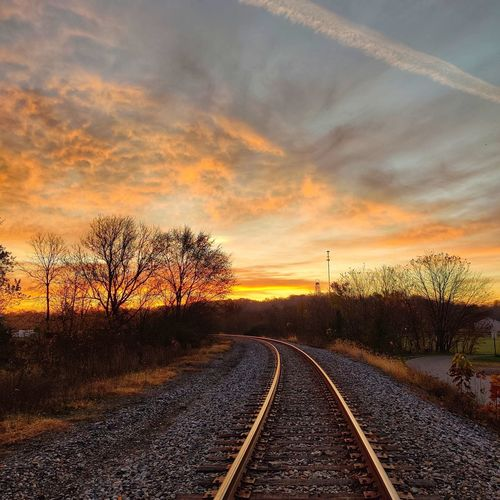 Railroad track amidst bare trees against sky during sunset